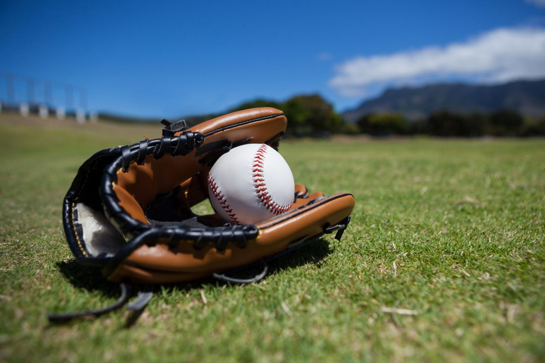 Close-up of baseball and glove on grassy field against sky Free Stock Images from PikWizard
