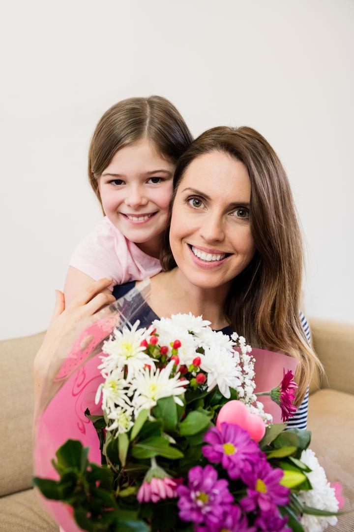 Mother receiving flower bouquet from her daughter in living room at home
