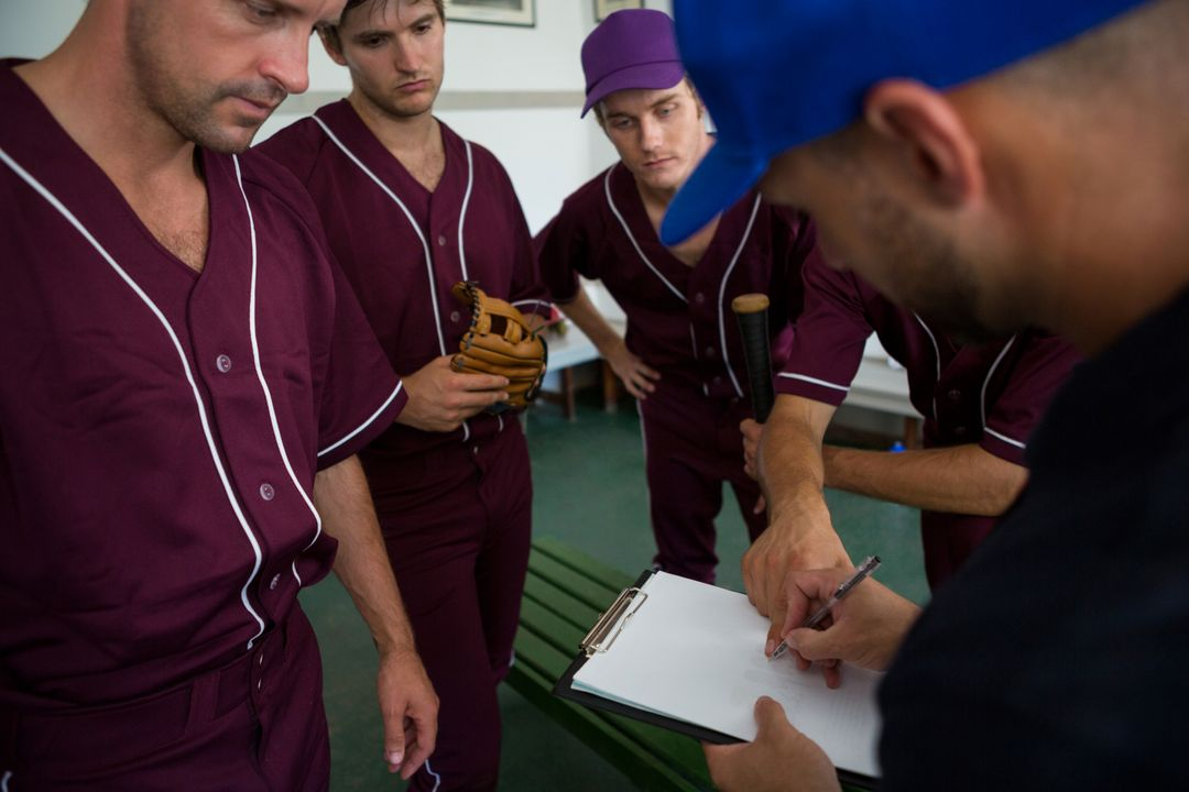 Close up of baseball team planning with coach while standing at locker room