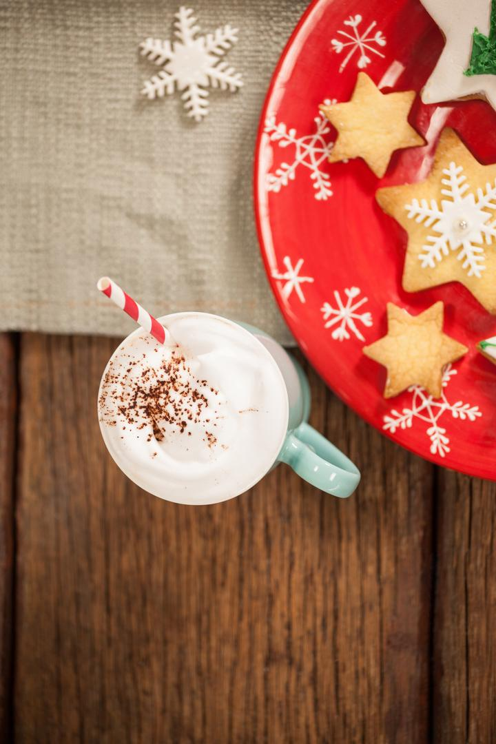 Sweet food and cappuccino on wooden table during christmas time
