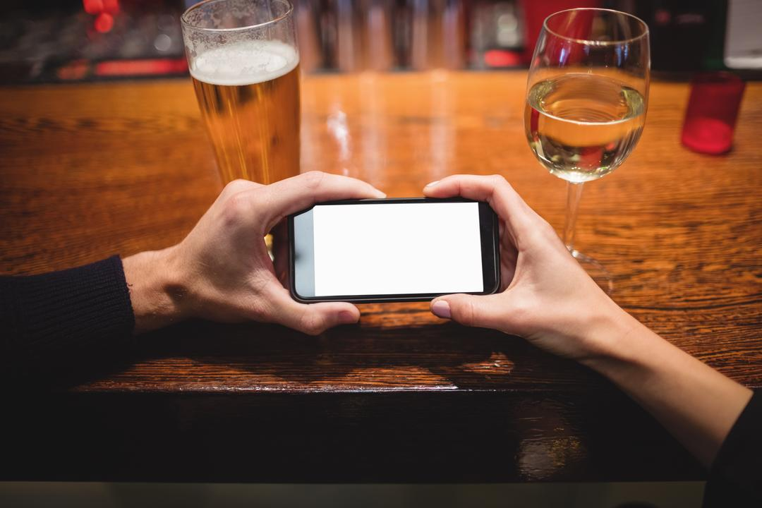 Close-up of couple using mobile phone at bar counter