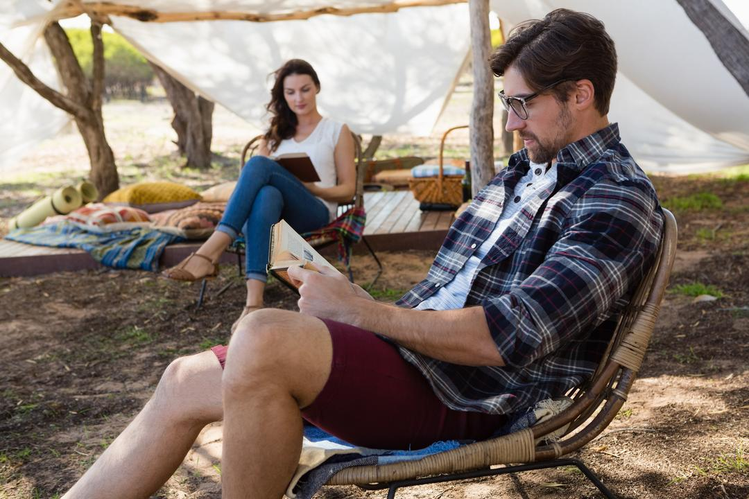 Couple reading books while sitting on chairs outside tent