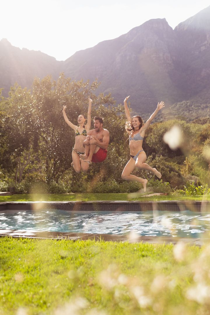 Happy male and female friends jumping in swimming pool at backyard
