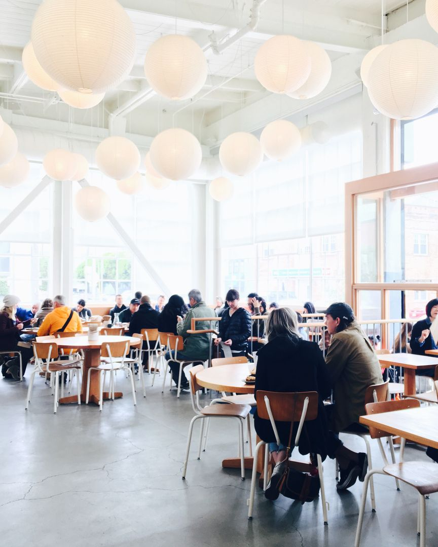 packed lunch hall with lights hanging overhead background