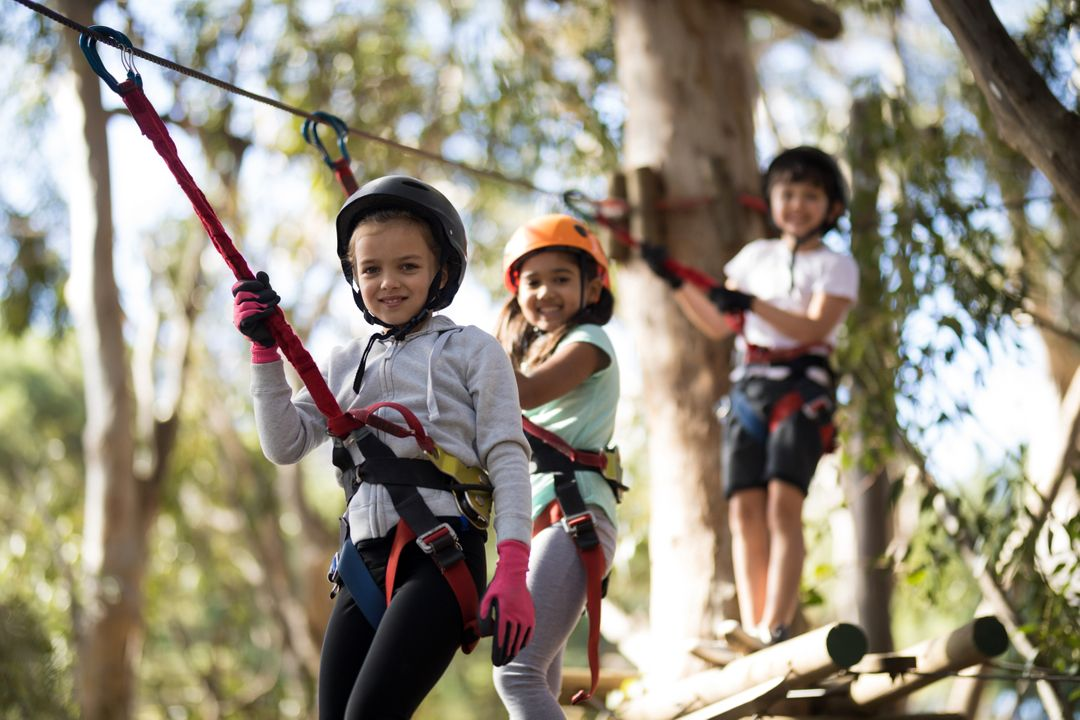 Portrait of happy kids crossing zip line on a sunny day Free Stock Images from PikWizard