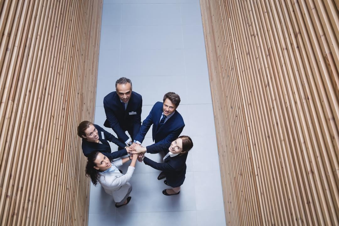 Overhead view of businesspeople stacking hands together in office
