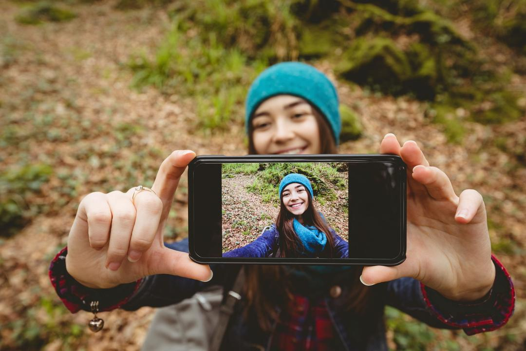 Woman taking selfie from mobile phone in forest