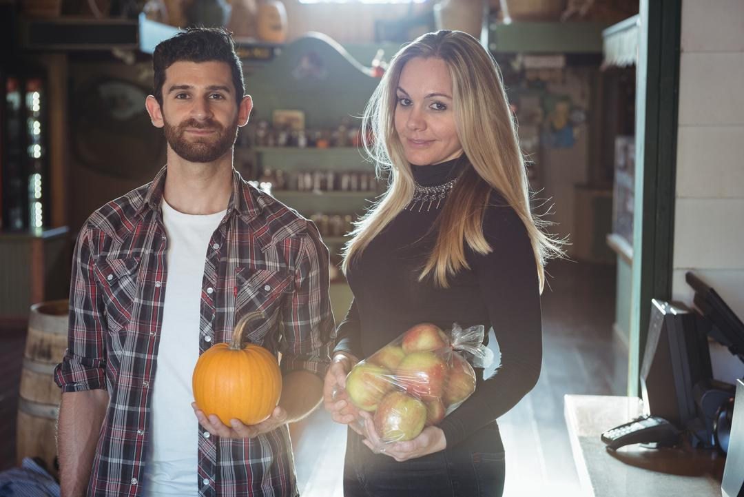 Portrait of couple holding vegetable and fruits in supermarket