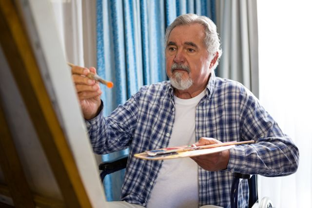 Senior man painting while sitting on wheelchair in nursing home