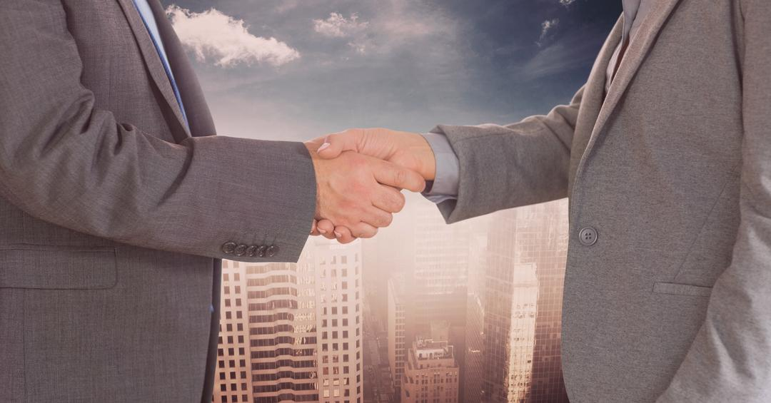 Digital composite of Midsection of businessmen doing handshake against city