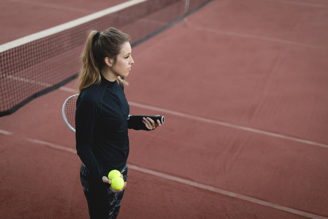 Thoughtful player holding tennis ball and racket in ground