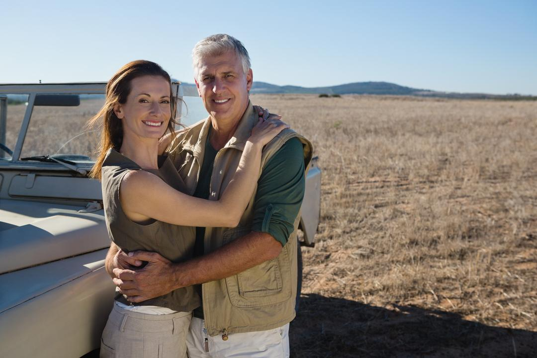 Portrait of smiling couple standing by off road vehicle on field Free Stock Images from PikWizard