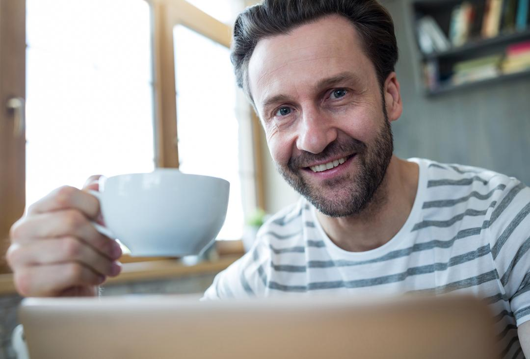 Portrait of smiling man holding a cup of coffee in coffee shop