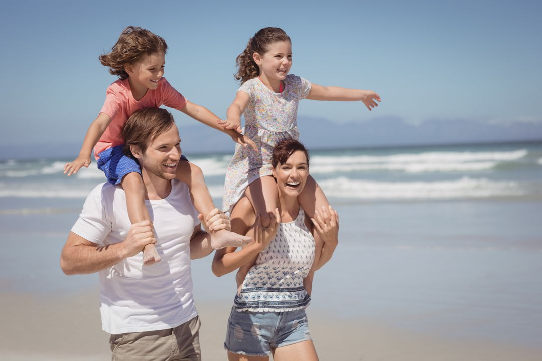 Cheerful family enjoying at beach during sunny day Free Stock Images from PikWizard