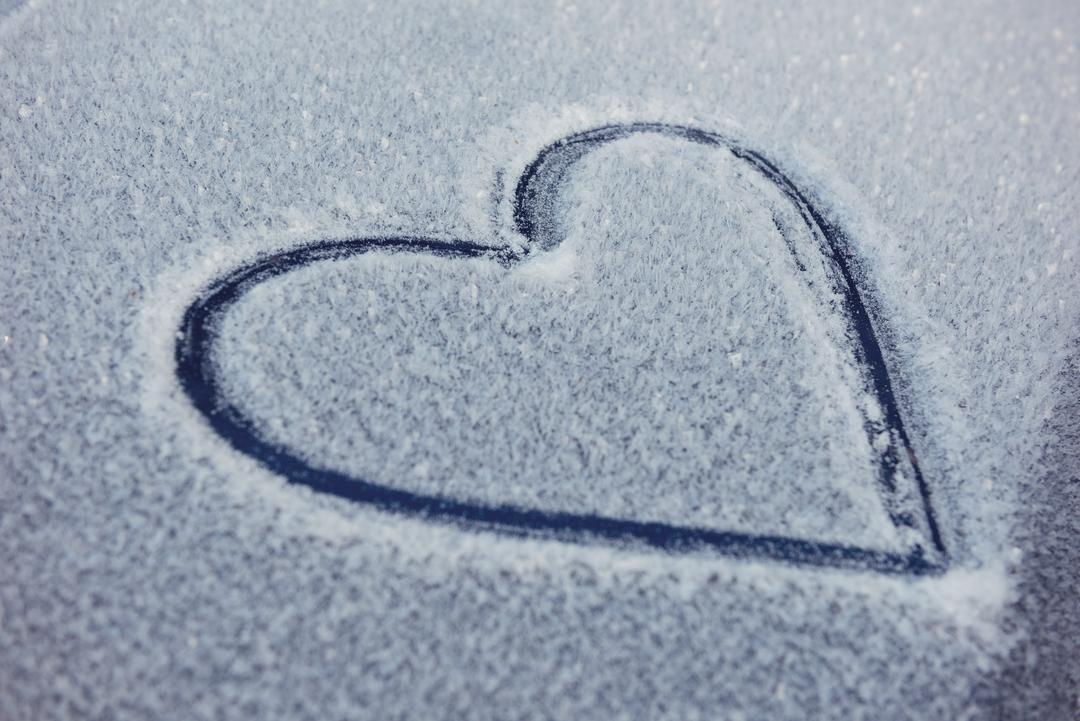 Close up of heart shape drawn on car bonnet covered with snow