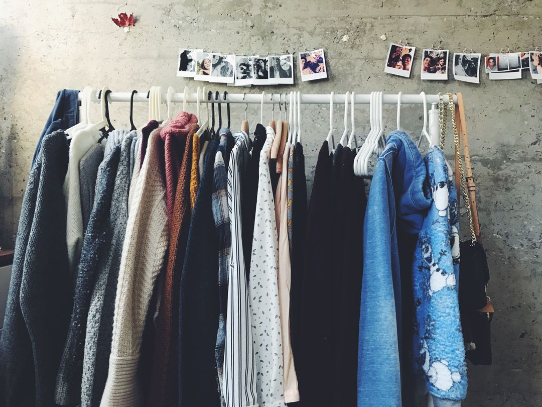 Photograph of clothes on a rack with polaroid images in the background