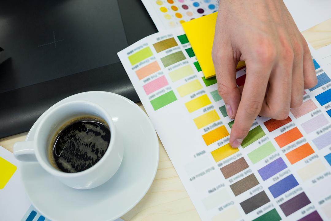 Hands of male graphic designer choosing color from color chart in office Free Stock Images from PikWizard