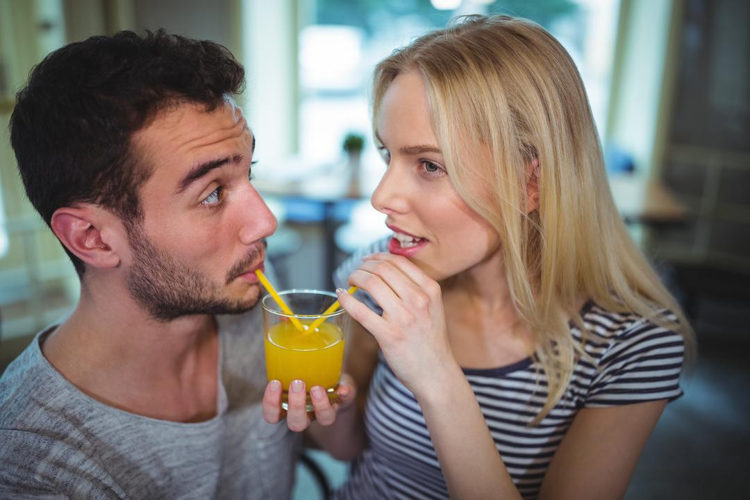 Couple having a glass of orange juice in café Free Stock Images from PikWizard