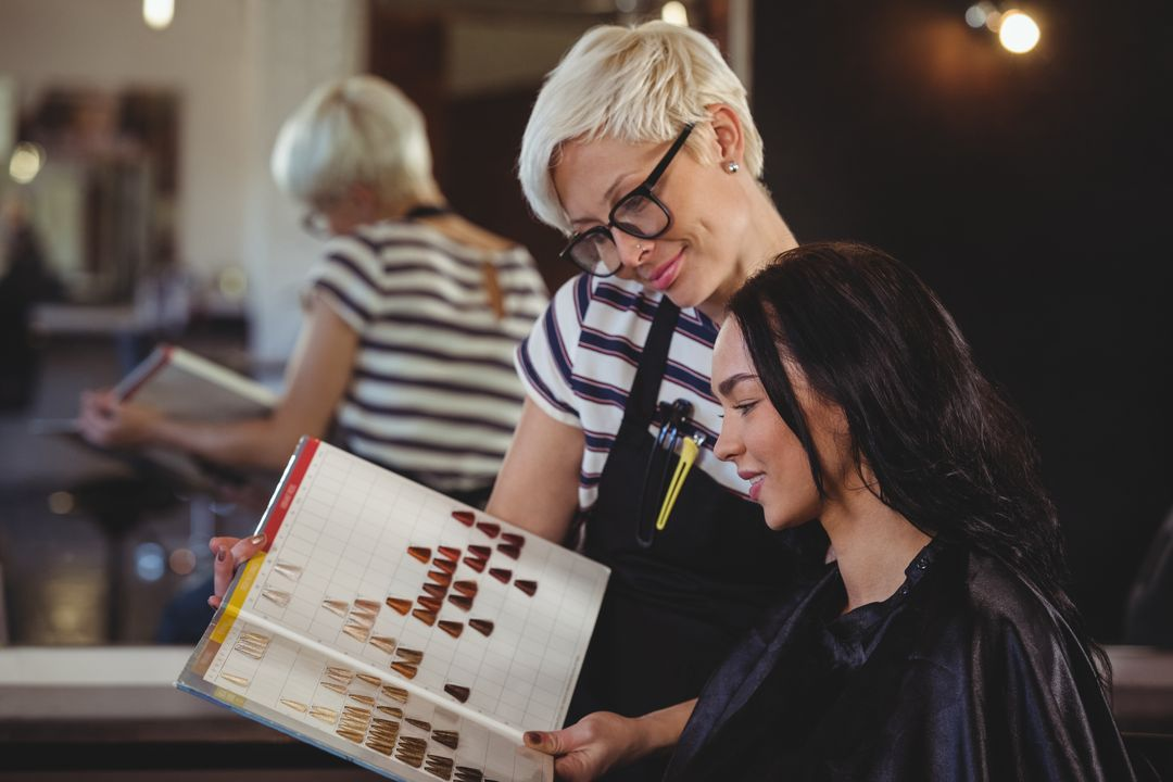 Woman selecting a hair color with stylist at the hair salon Free Stock Images from PikWizard