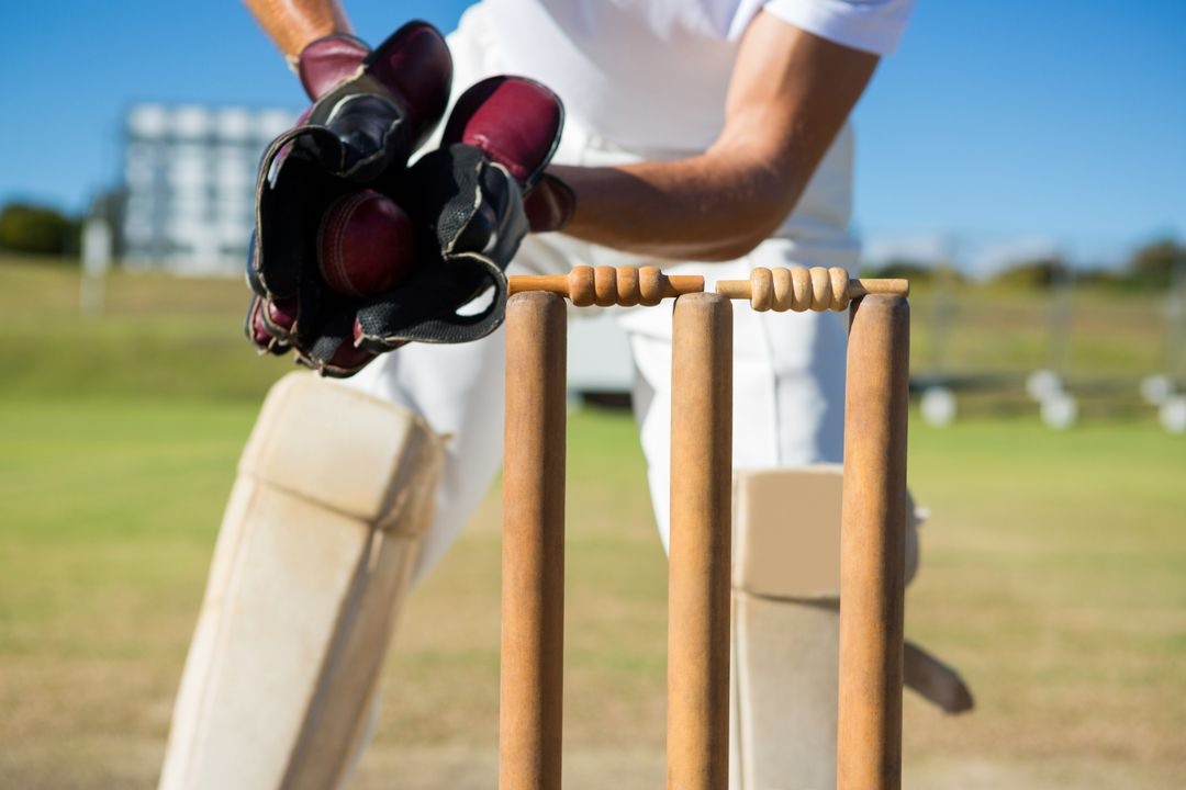 Cropped image of wicket keeper standing by stumps during match on sunny day Free Stock Images from PikWizard