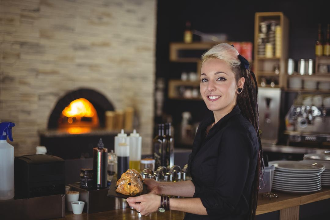Portrait of waitress holding tray of muffins at counter in cafe
