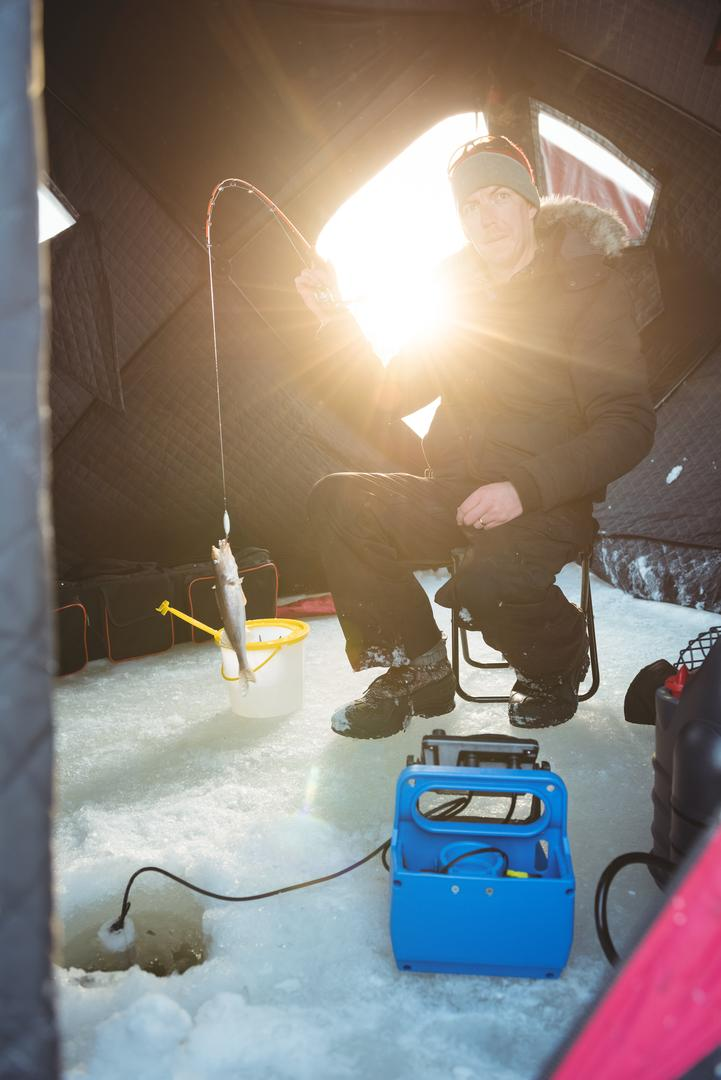 Portrait of Ice fisherman sitting on chair with fish in his rod