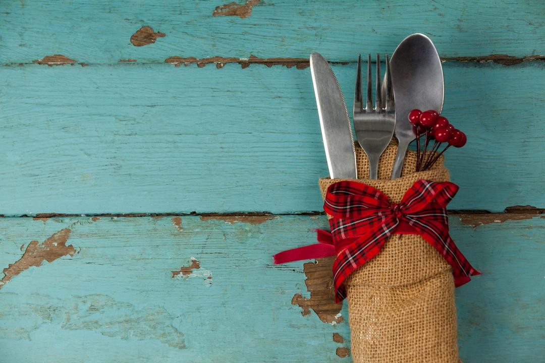 Cutlery tied up with sack on a plank