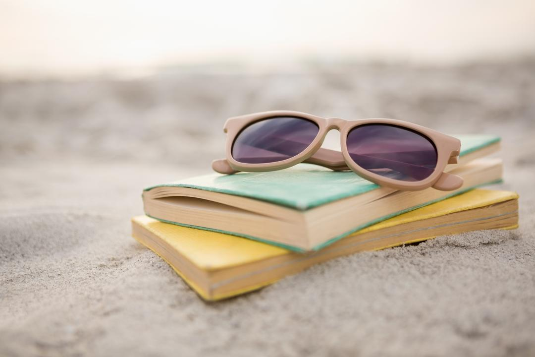 Sunglasses and books on sand at beach