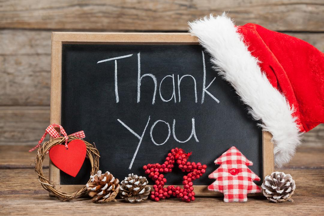 Thank you message on slate with chirstmas decorations on wooden table during christmas time