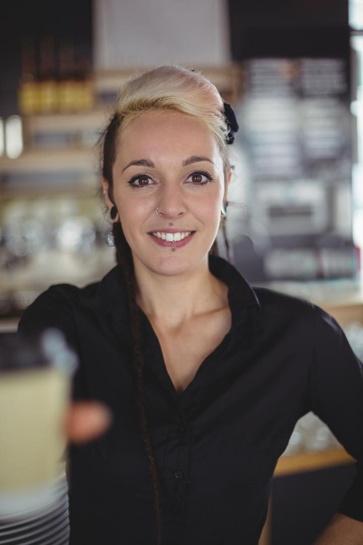 Portrait of waitress standing with disposable coffee cup in café