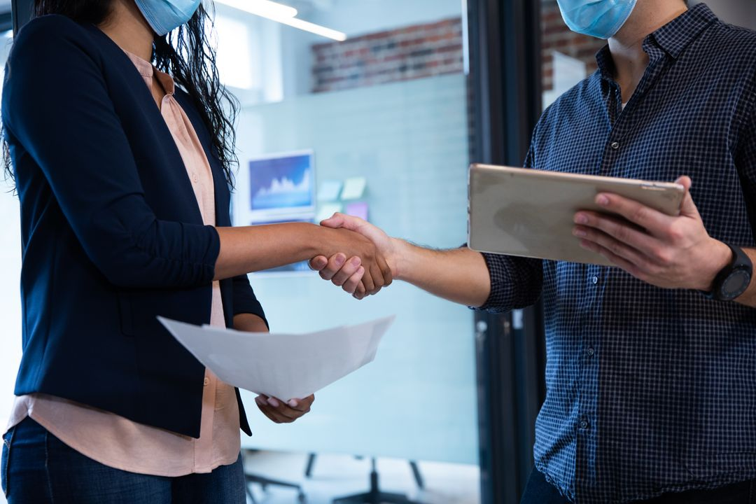 Mixed race woman and Caucasian man working in a casual office, wearing face masks, shaking hands. Colleagues in the workplace during Coronavirus Covid 19 pandemic. Free Stock Images from PikWizard