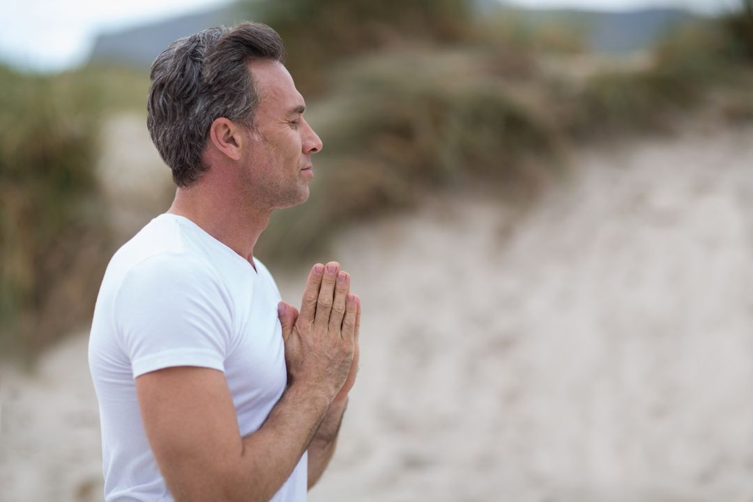 Mature man doing meditation on the beach Free Stock Images from PikWizard