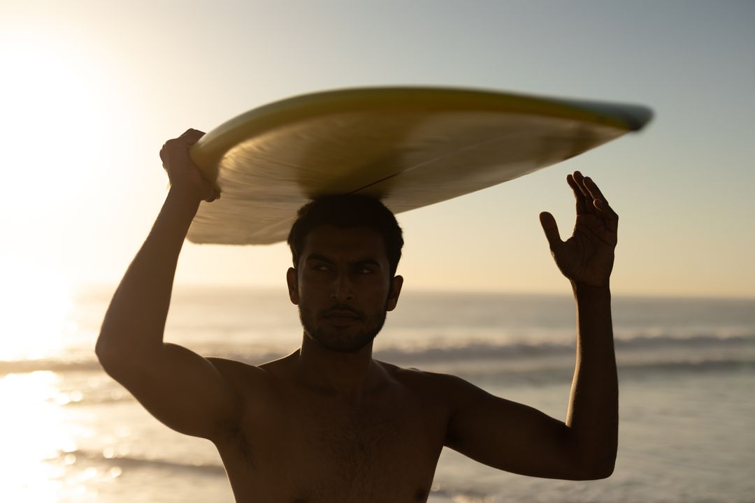 Young man standing with surfboard on the beach
