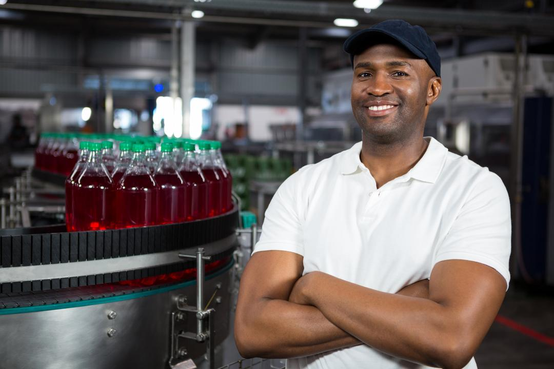 Portrait confident male worker standing in cold drink factory