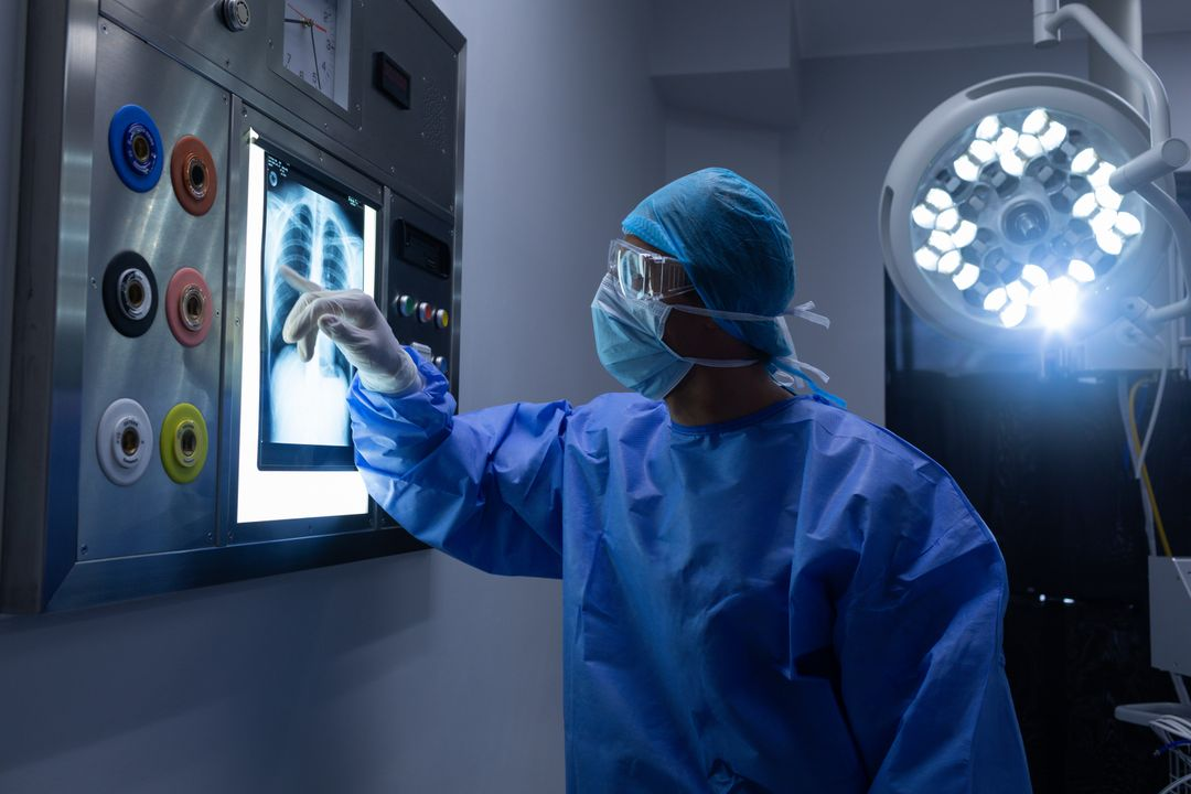 MSide view of Caucasian male surgeon examining x-ray on light box in operation theater at hospital