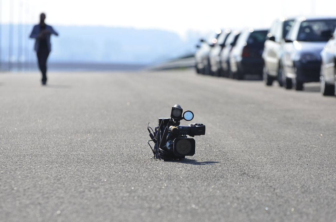 Camera left in the middle of a road with parked cars