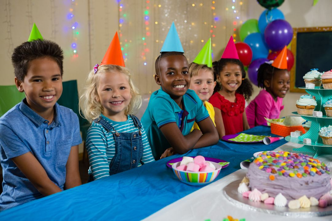 Portrait of smiling children sitting at table during birthday Free Stock Images from PikWizard