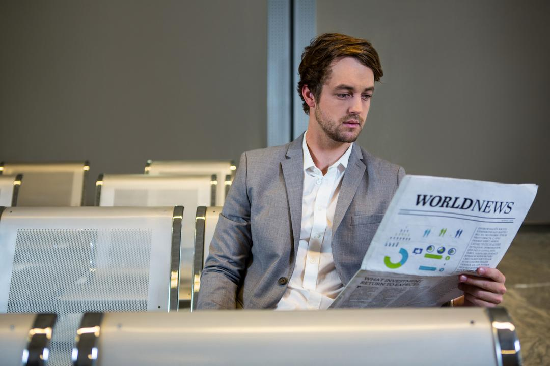 Businessman sitting in waiting area and reading newspaper in airport