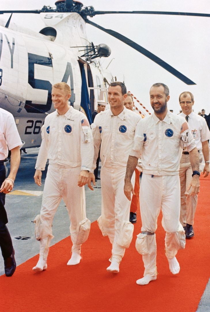 S69-27920 (13 March 1969) --- The Apollo 9 crew men walk on a red carpet after arriving aboard the prime recovery ship, USS Guadalcanal. Left to right, are astronauts Russell L. Schweickart, David R. Scott, and James A. McDivitt. They are walking from the recovery helicopter which picked them up from the splashdown area. Splashdown occurred at 12:00:53 p.m. (EST), March 13, 1969, only 4.5 nautical miles from the USS Guadalcanal to conclude a successful 10-day Earth-orbital space mission.