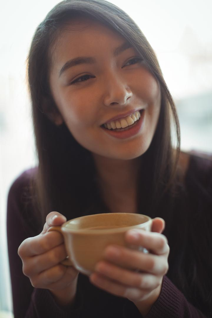 Smiling woman having cup of coffee at café