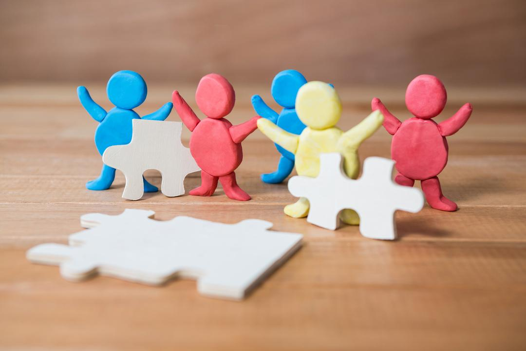 Colorful clay figures standing together with jigsaw pieces