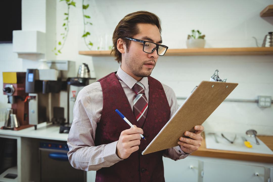 Man writing with pen on clipboard in coffee shop