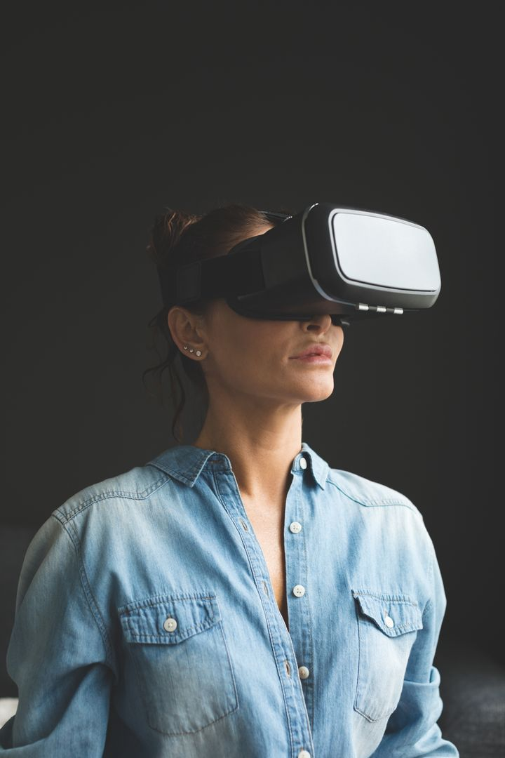 Beautiful woman using virtual reality headset in a comfortable home