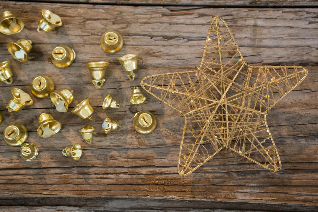 Christmas bells and star on wooden plank during christmas time