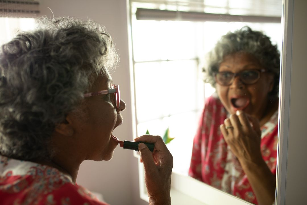 A senior African American woman at home, social distancing and self isolation in quarantine lockdown during coronavirus covid 19 epidemic, putting lipstick on looking in a mirror Free Stock Images from PikWizard