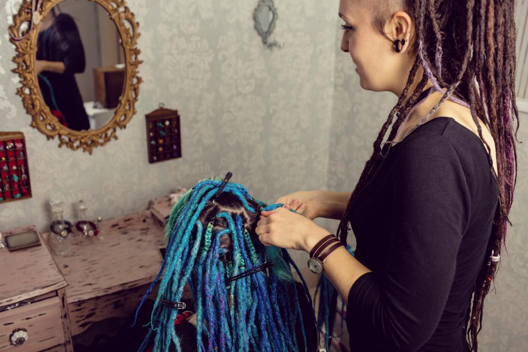 Beautician styling clients hair in dreadlocks shop