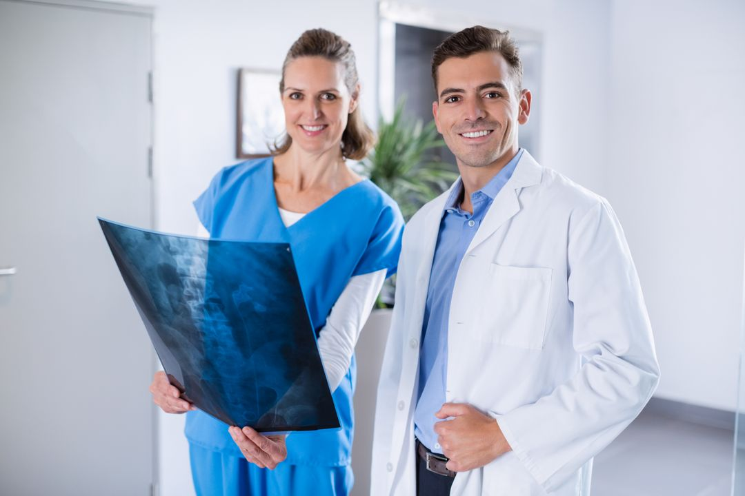Portrait of two doctors standing with patients x-ray in hospital corridor Free Stock Images from PikWizard