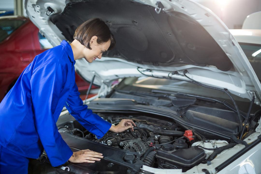 Female mechanic examining a car in repair garage