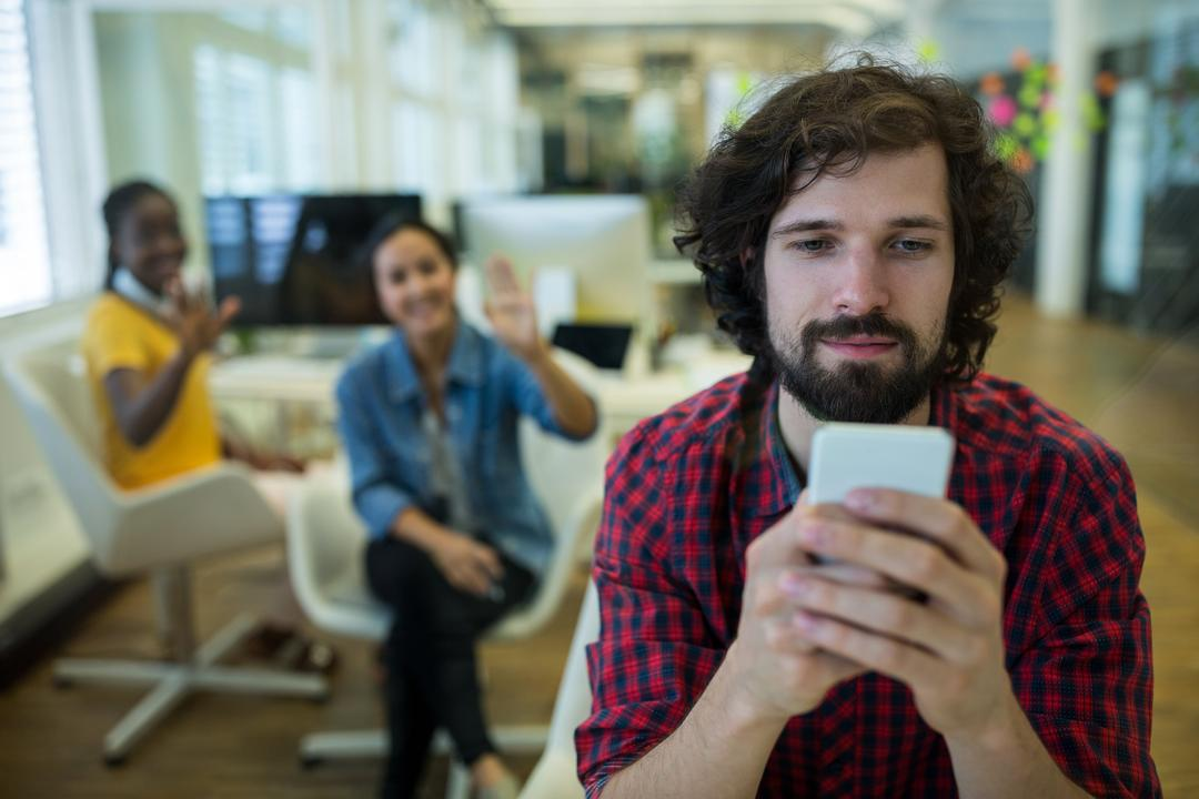 Male graphic designer using mobile phone in office