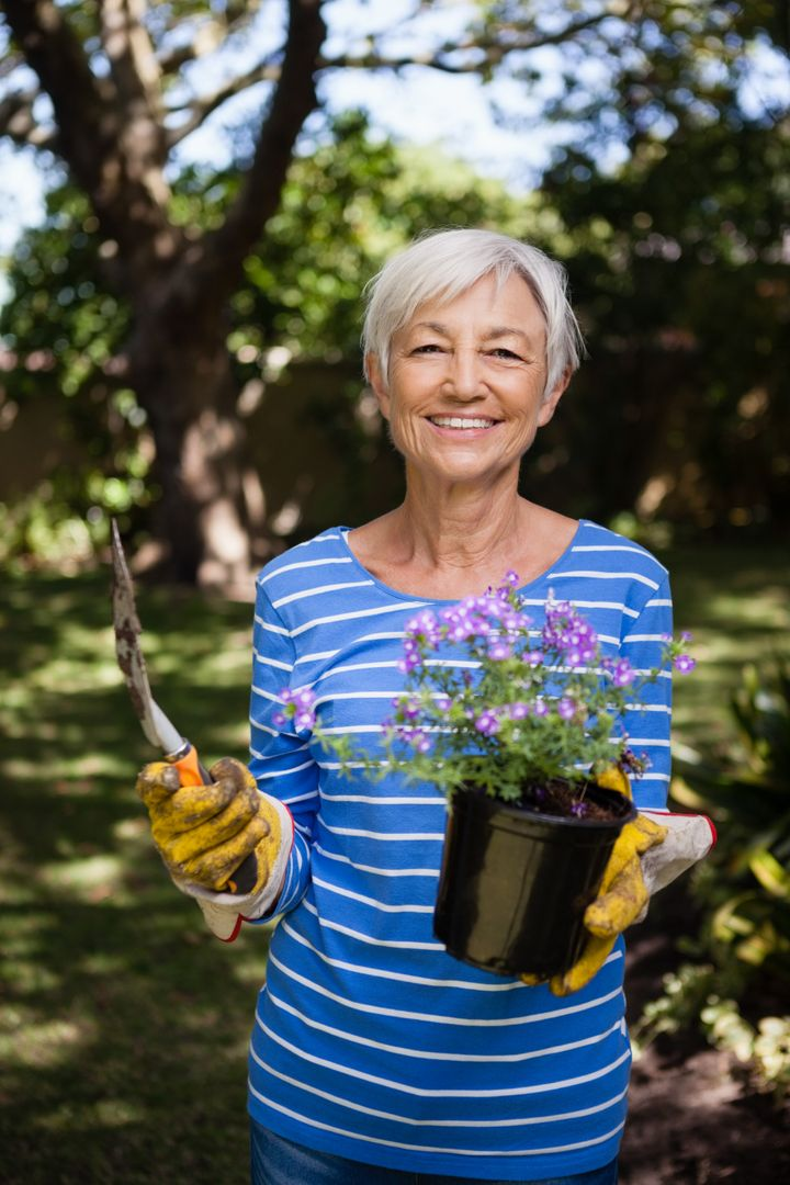 Portrait of smiling senior woman holding potted plant and trowel at backyard Free Stock Images from PikWizard